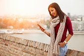 Happy woman with a smart phone outdoors