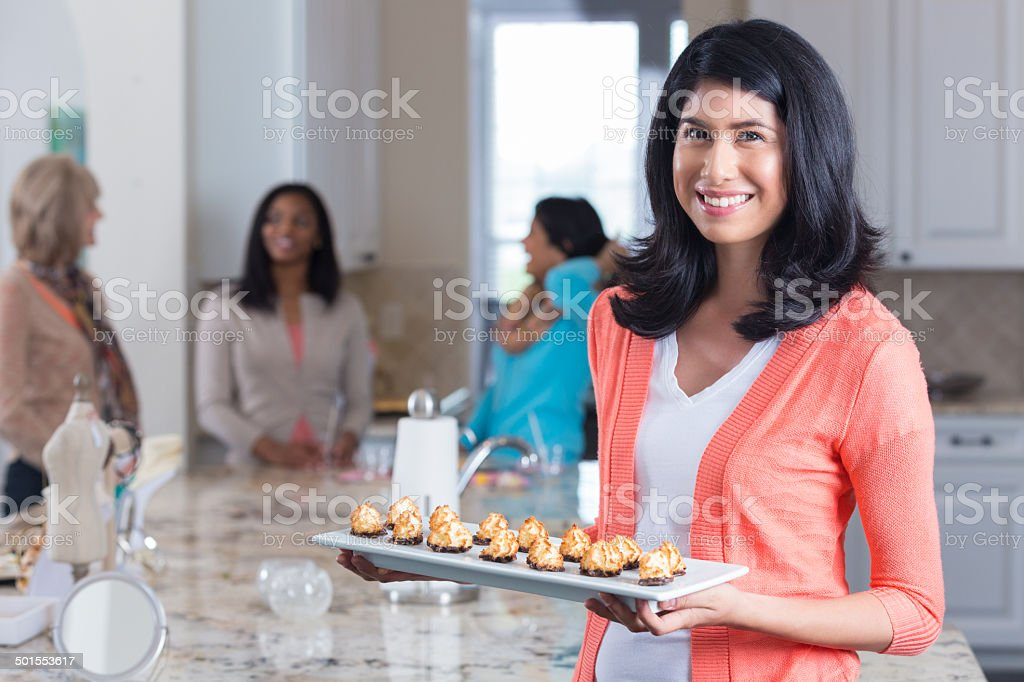 Happy woman with appetizers hosting home sales party stock photo