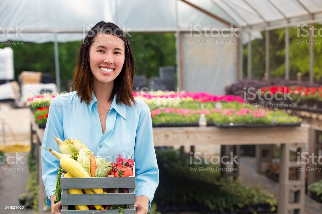 Happy woman with basket of fresh produce stock photo