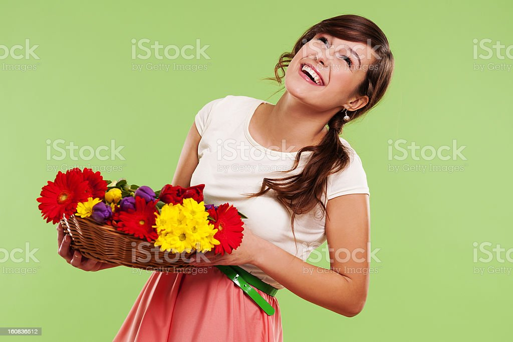 Happy woman with basket of spring flowers royalty-free stock photo