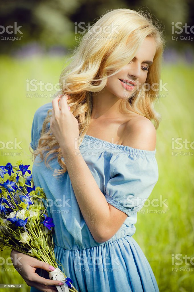 Happy woman with bouquet of purple flowers stock photo