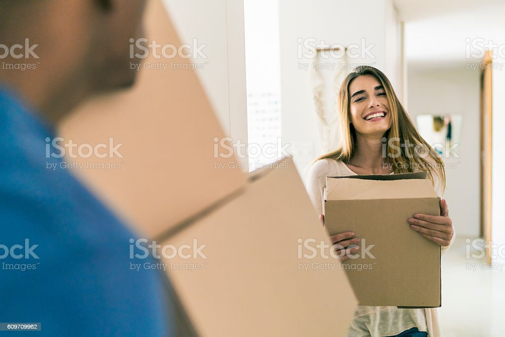Happy woman with cardboard box looking at man stock photo