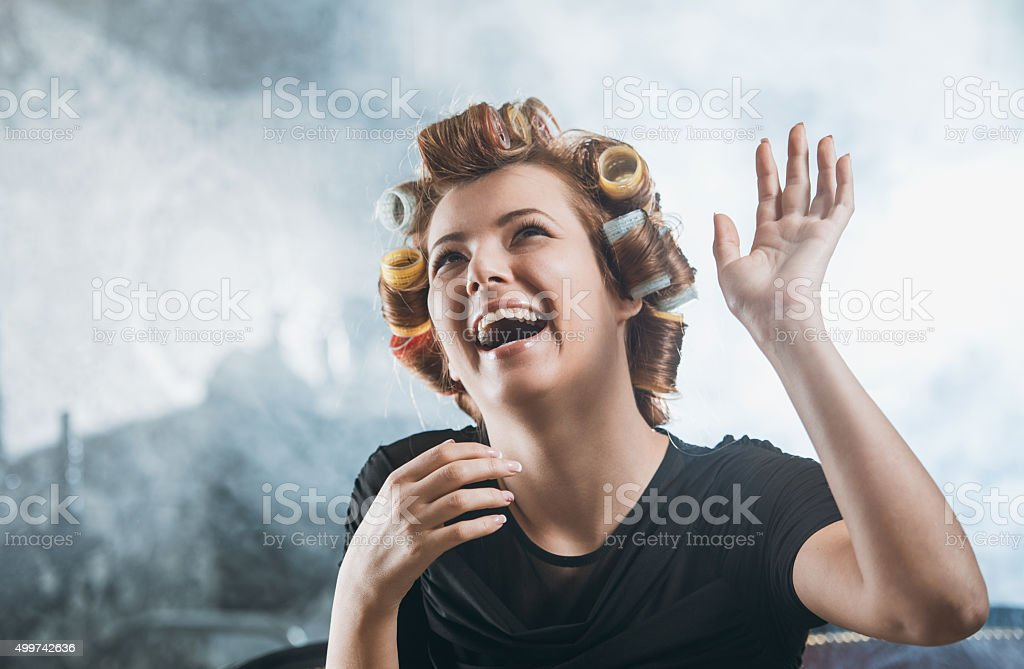 Happy woman with curlers in hair laughing. stock photo