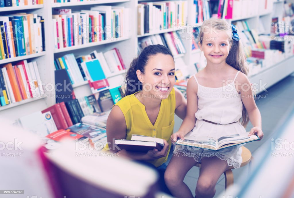 Happy woman with girl holding open book stock photo