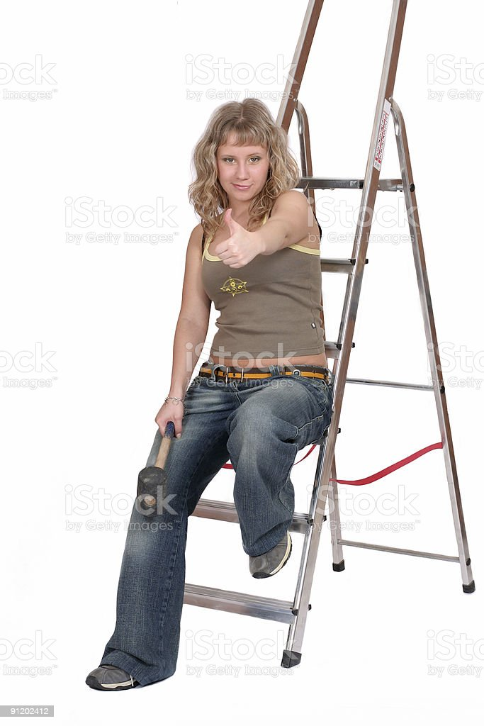 happy woman with hammer on ladder royalty-free stock photo