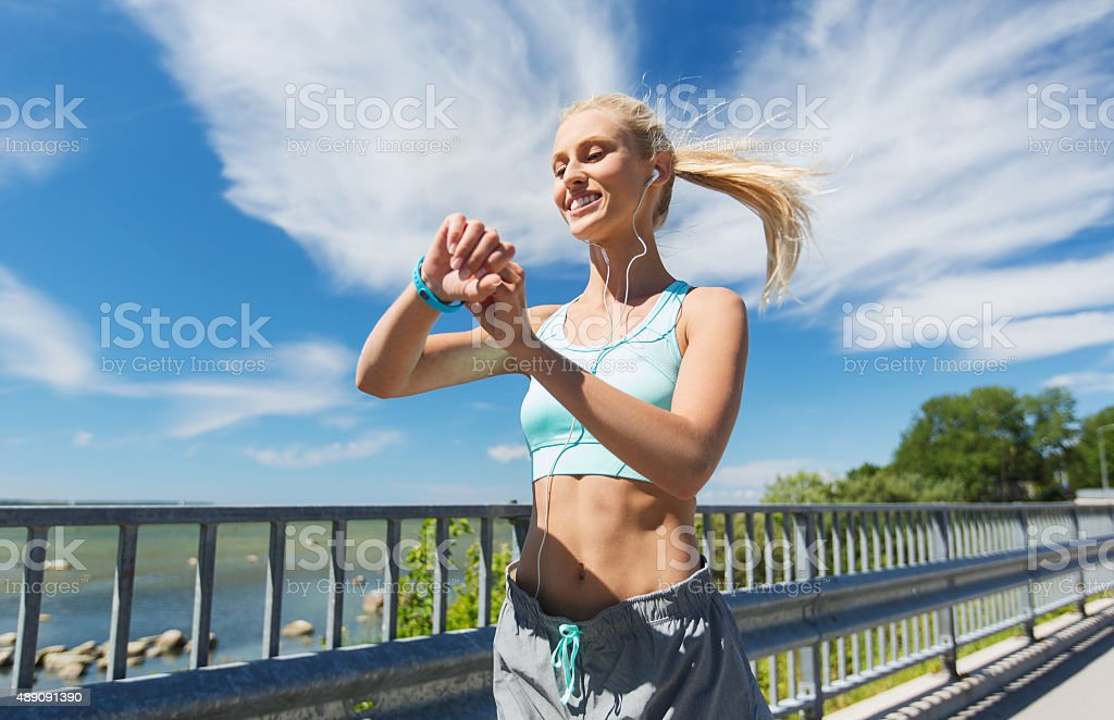 happy woman with heart rate watch and earphones stock photo
