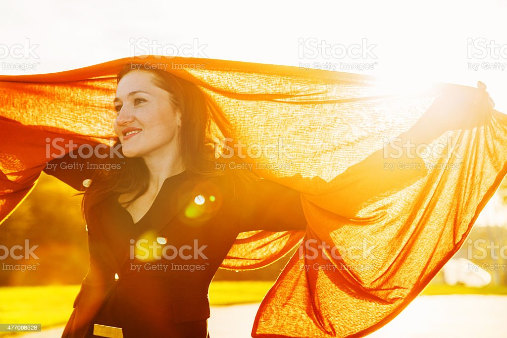 Happy woman with long brown fluttering scarf on sunset stock photo