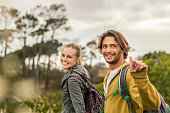 Happy woman with man gesturing on field during hiking