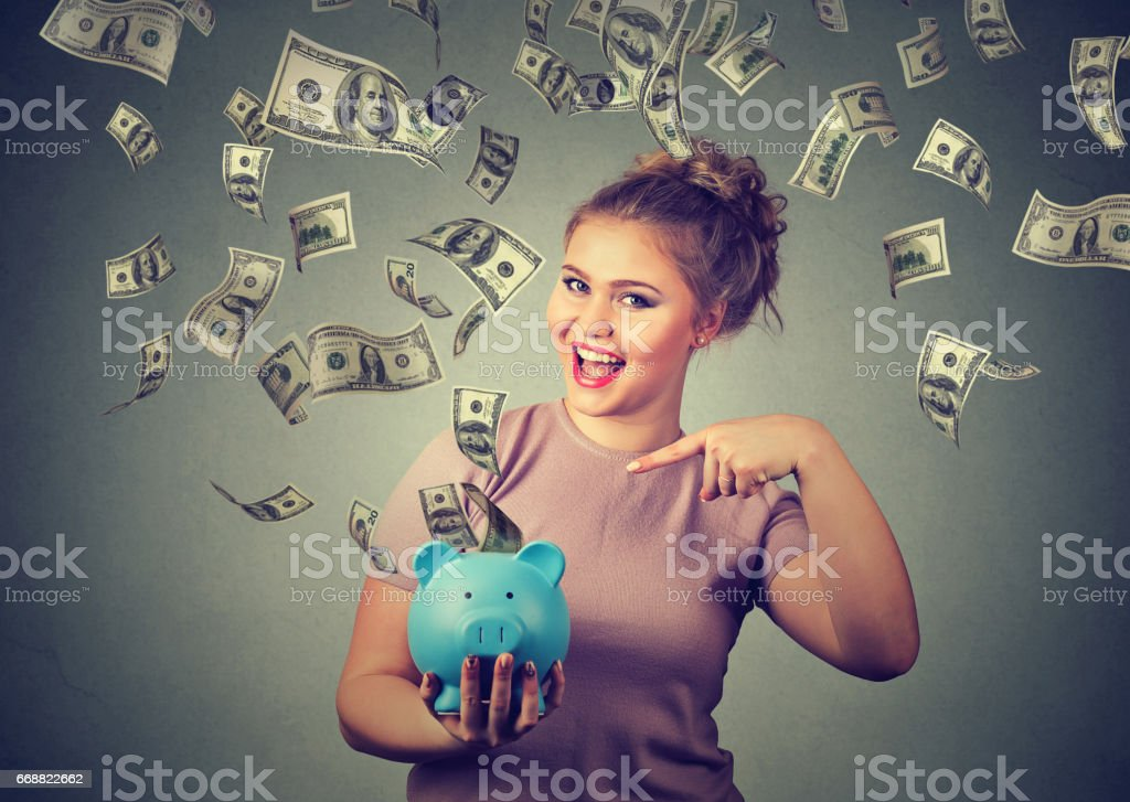 happy woman with piggy bank ecstatic celebrates success under a money rain falling down dollar bills banknotes stock photo