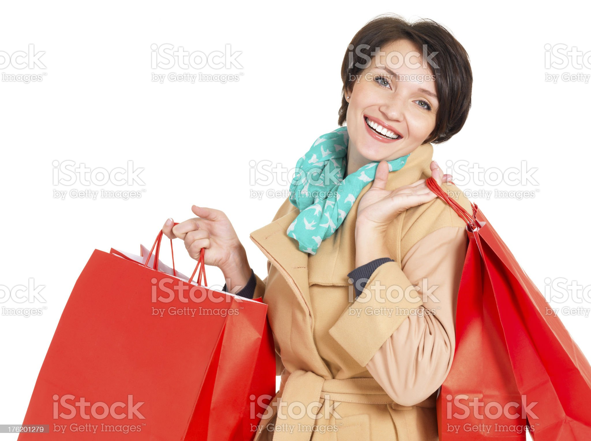 Happy woman with shopping bags in beige autumn coat royalty-free stock photo