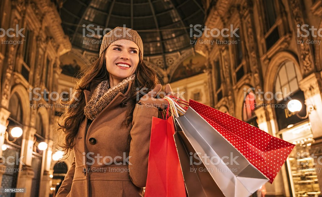 Happy woman with shopping bags in Galleria Vittorio Emanuele II stock photo