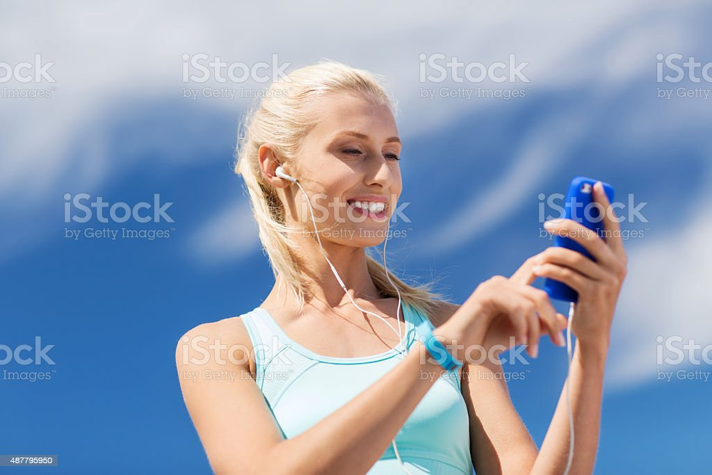 happy woman with smartphone and earphones outdoors stock photo