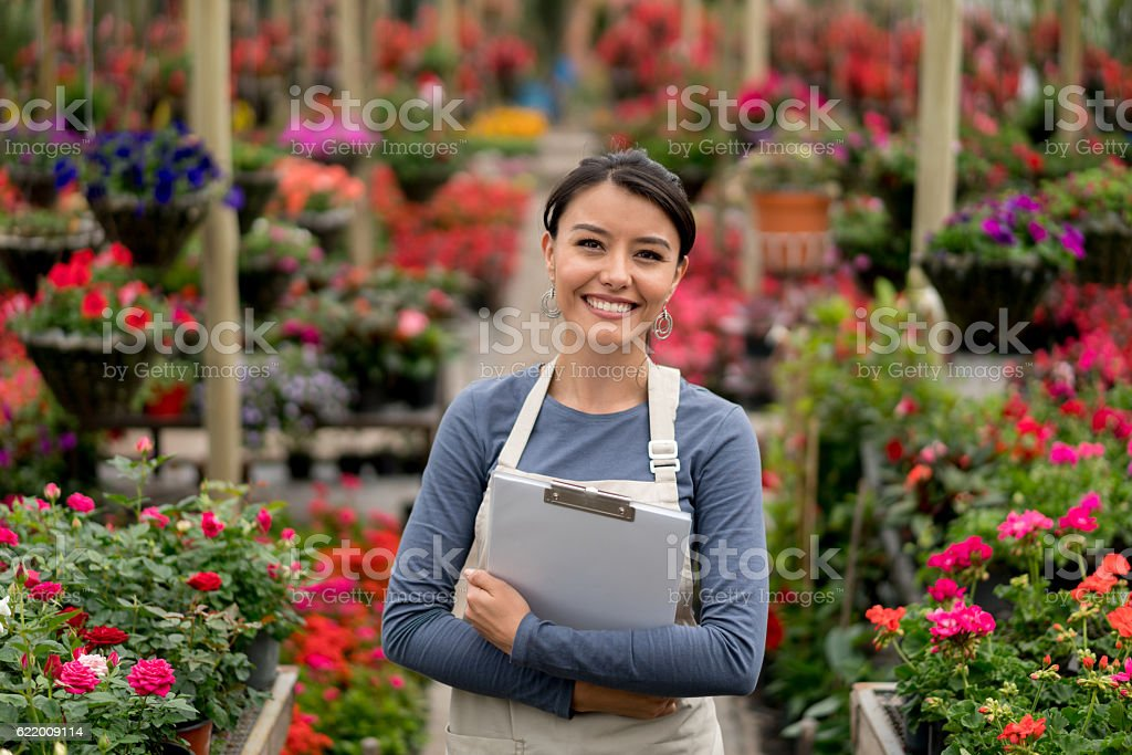 Happy woman working at a greenhouse stock photo