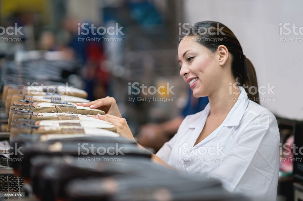 Happy woman working at a shoe-making factory stock photo