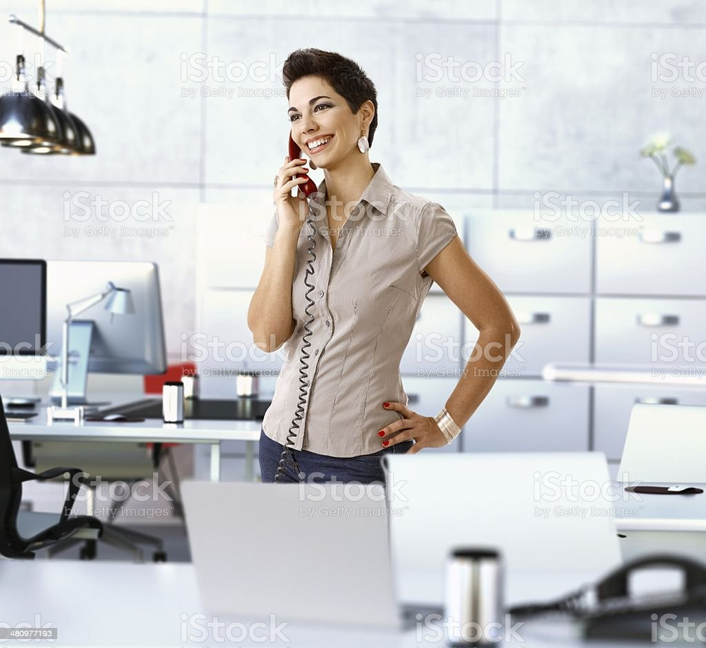 Happy woman working at office talking on phone stock photo