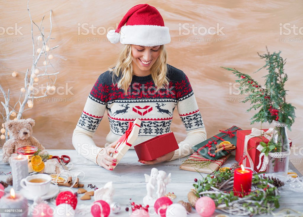 Happy woman wrapping Christmas present box stock photo