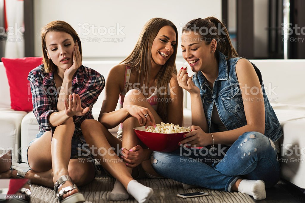 Happy women at home eating popcorns and ignoring their friend. stock photo