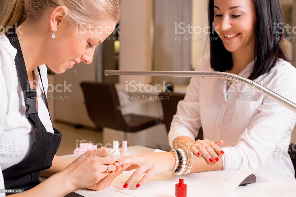 Happy women doing manicure stock photo