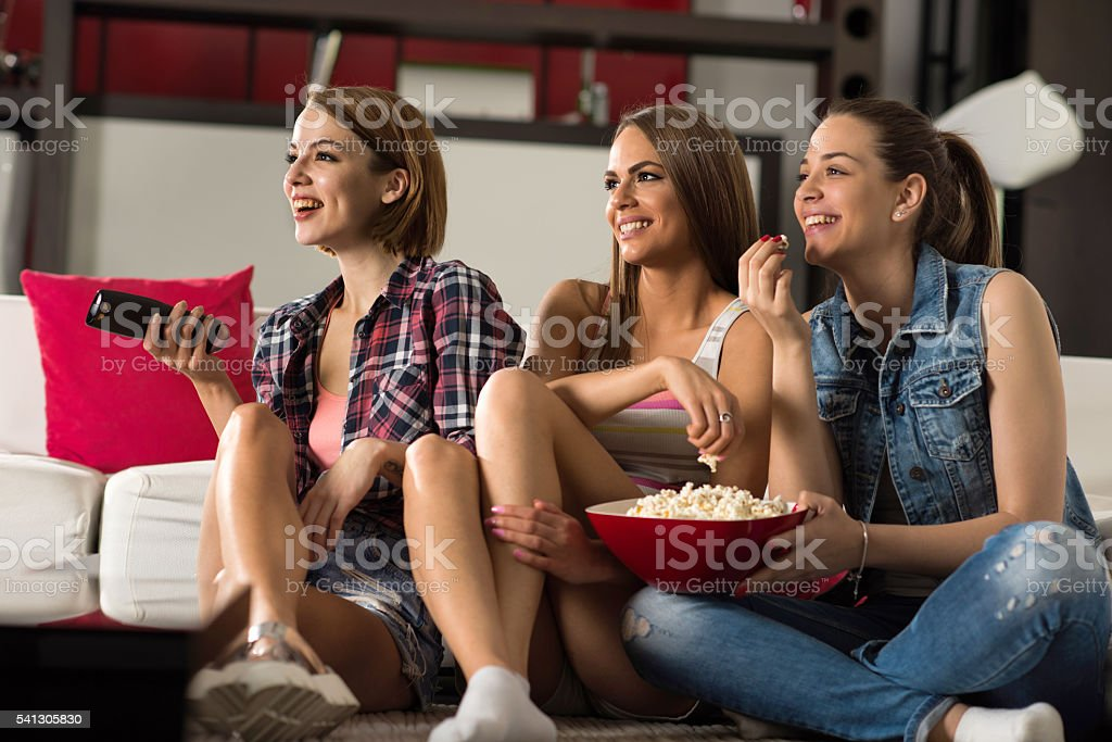 Happy women eating popcorns and watching TV at home. stock photo