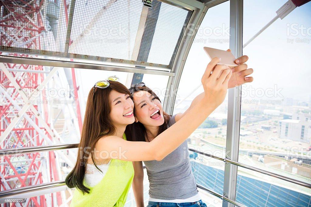 happy women girlfriends taking a selfie in ferris wheel stock photo