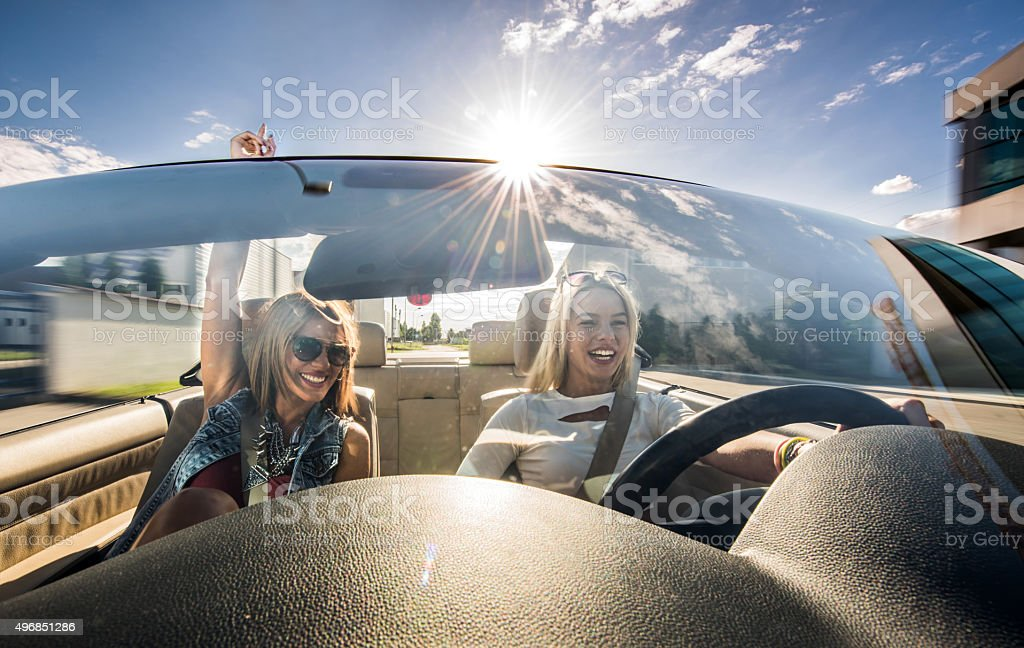 Happy women having fun on a road trip in convertible. stock photo