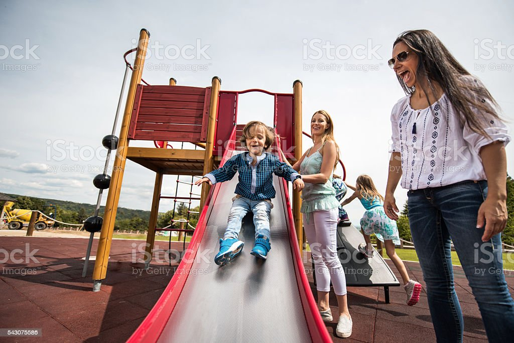 Happy women having fun with their children at the playground. stock photo
