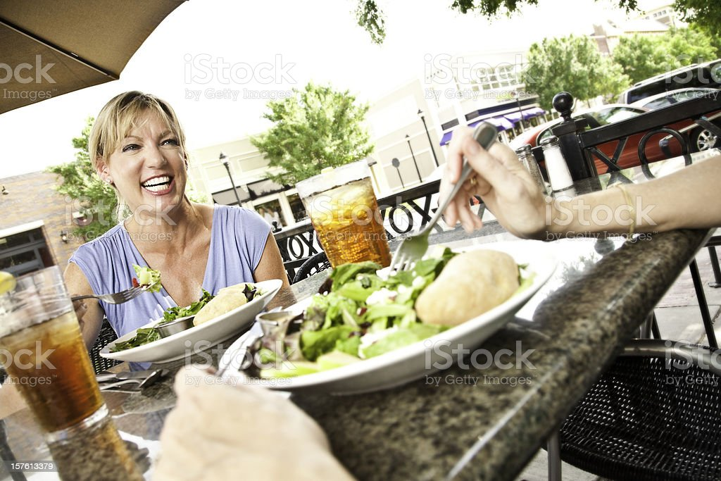 Happy Women Having Lunch Together on Outdoor Patio stock photo