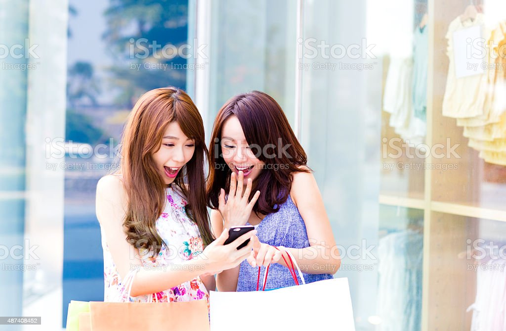 Happy Women holding shopping bags and watching Phone stock photo