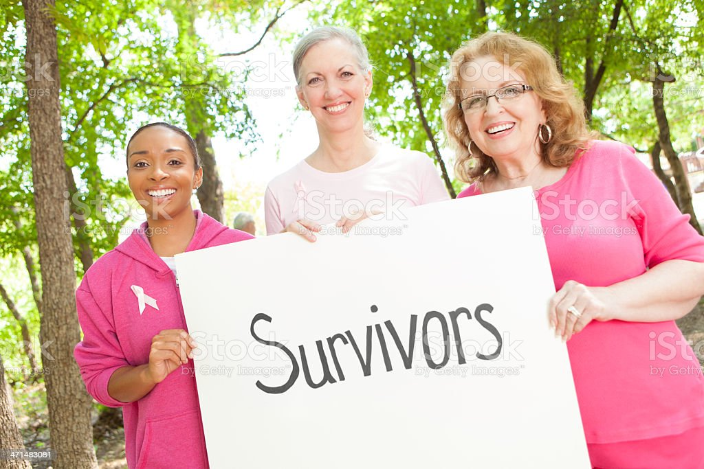 Happy women holding Survivors sign at breast cancer awareness race stock photo