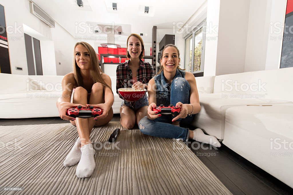 Happy women playing video games and having fun at home. stock photo
