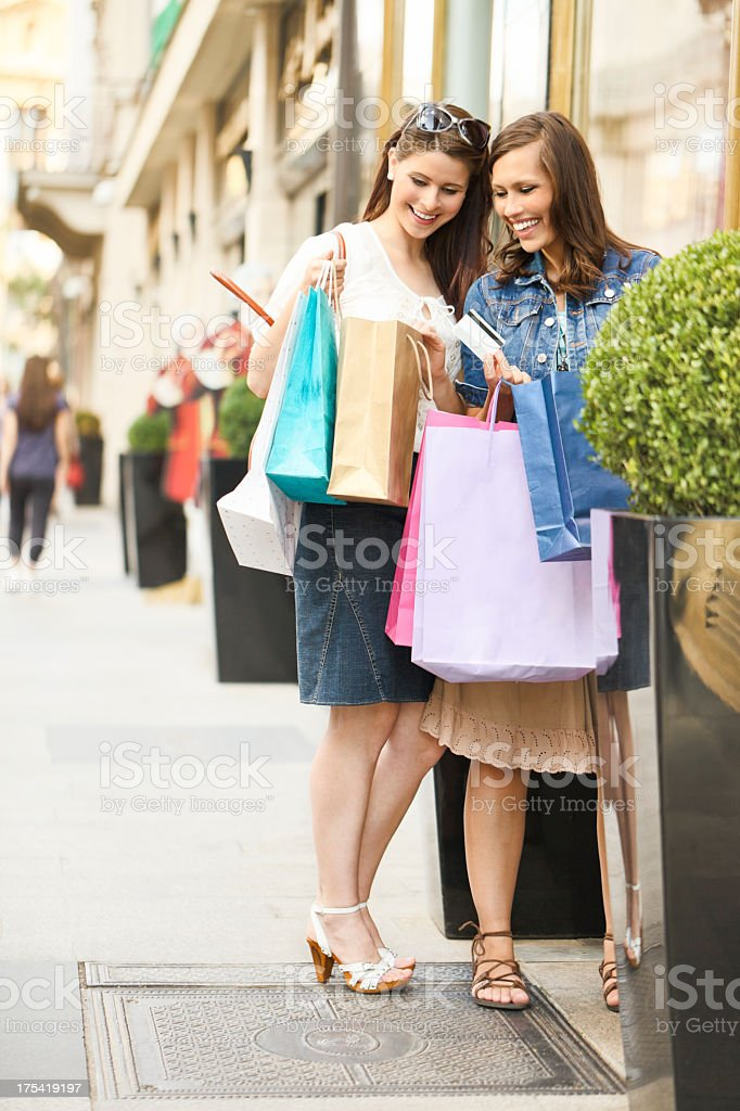 Happy women posing with shopping bags stock photo