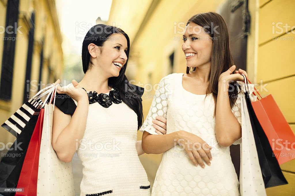 Happy women posing with shopping bags royalty-free stock photo