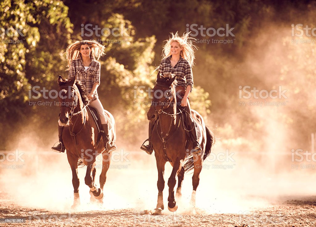 Happy women practicing with their horses in nature. stock photo