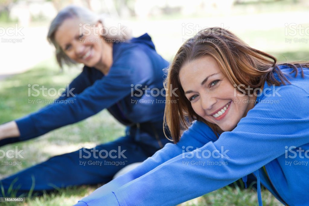 Happy Women Stretching Legs While Exercising at a Park royalty-free stock photo