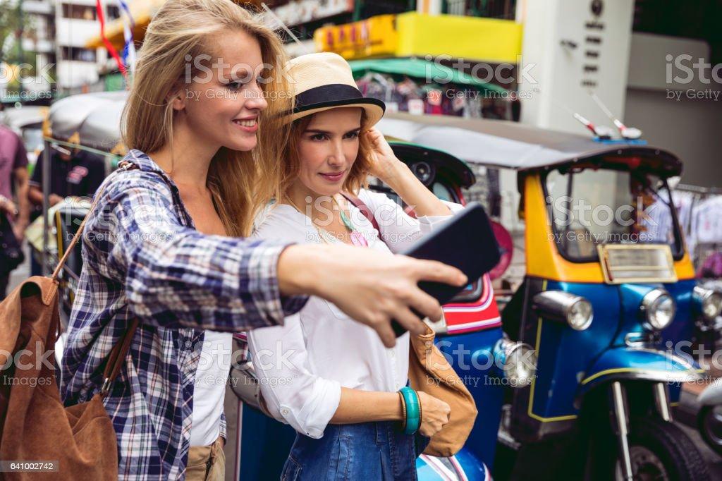 Happy women tourist taking a selfie in Khao San Road - Bangkok stock photo