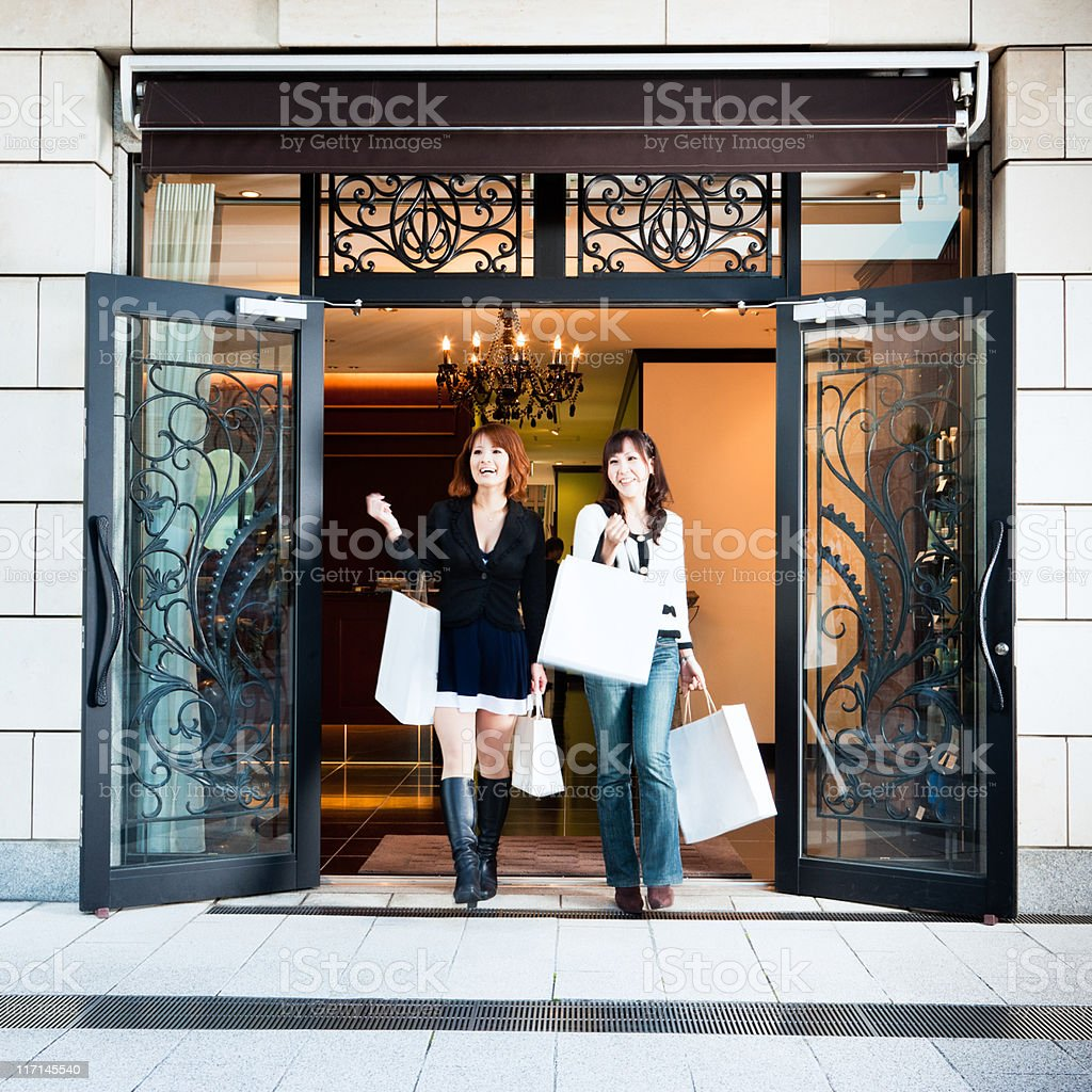 Happy women walking out of luxury boutique stock photo