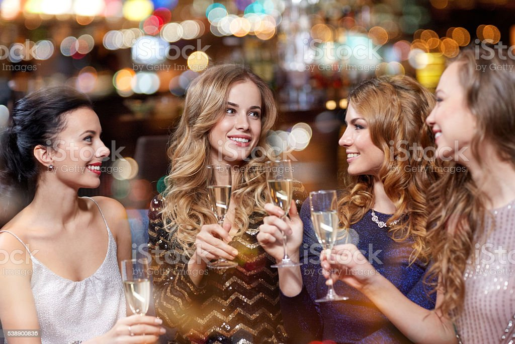 happy women with champagne glasses at night club stock photo