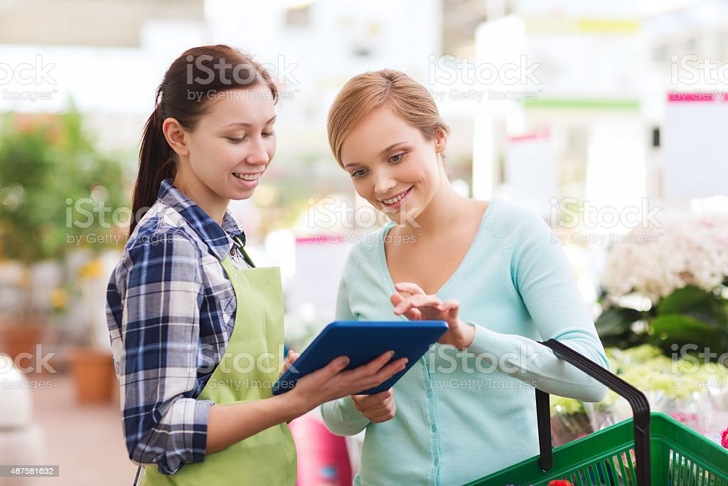 happy women with tablet pc in greenhouse stock photo