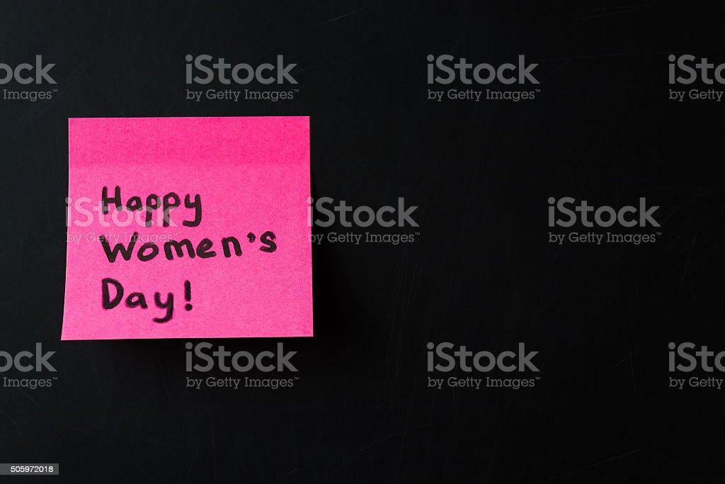 Happy Women's Day. Pink sticker on black chalkboard stock photo