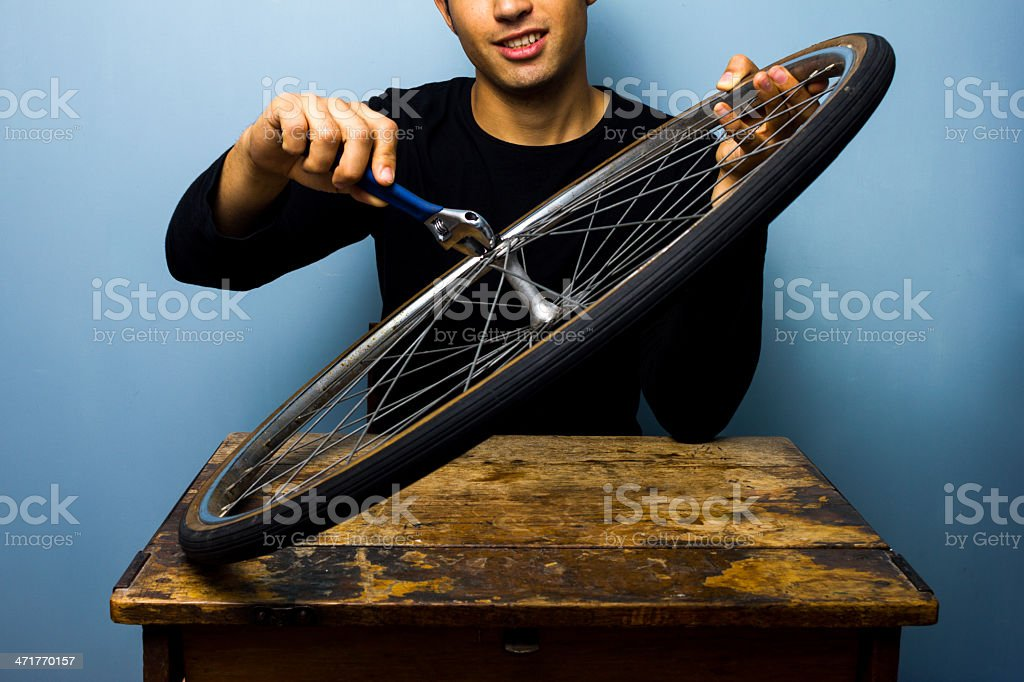 Happy worker fixing bicycle tyre royalty-free stock photo