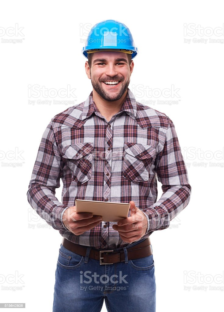 Happy worker in blue helmet using a digital tablet stock photo
