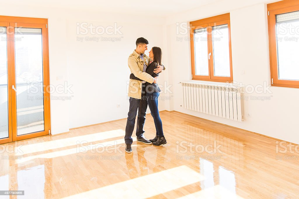 Happy young adult couple in their new empty flat stock photo