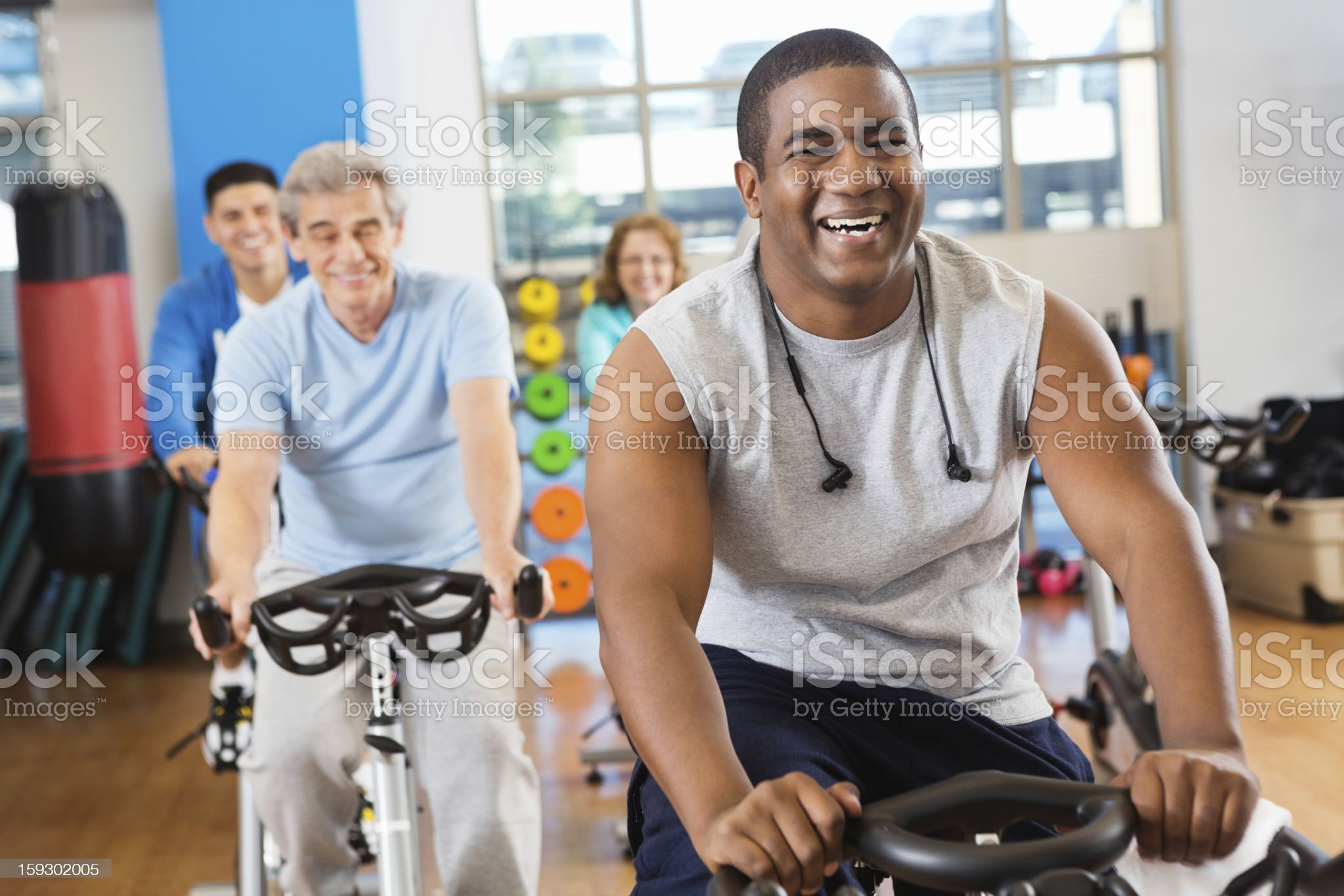 Happy young adult cycling in his fitness club class royalty-free stock photo