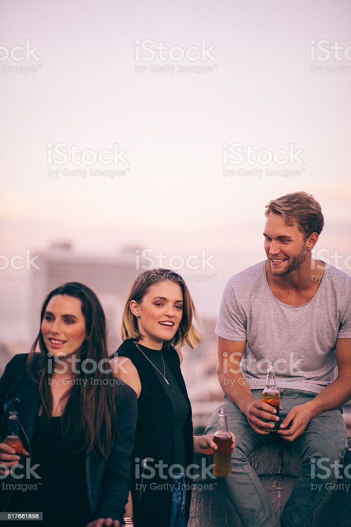 Happy young adult friends enjoying a rooftop party stock photo