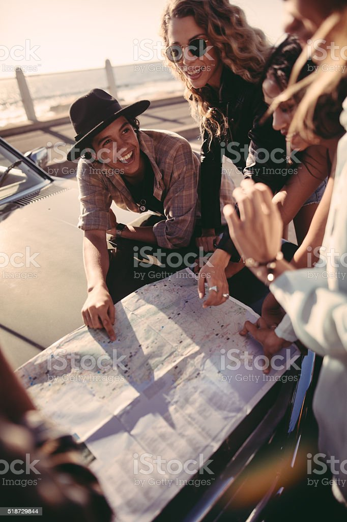 Happy young adult friends planning their road trip at beach stock photo