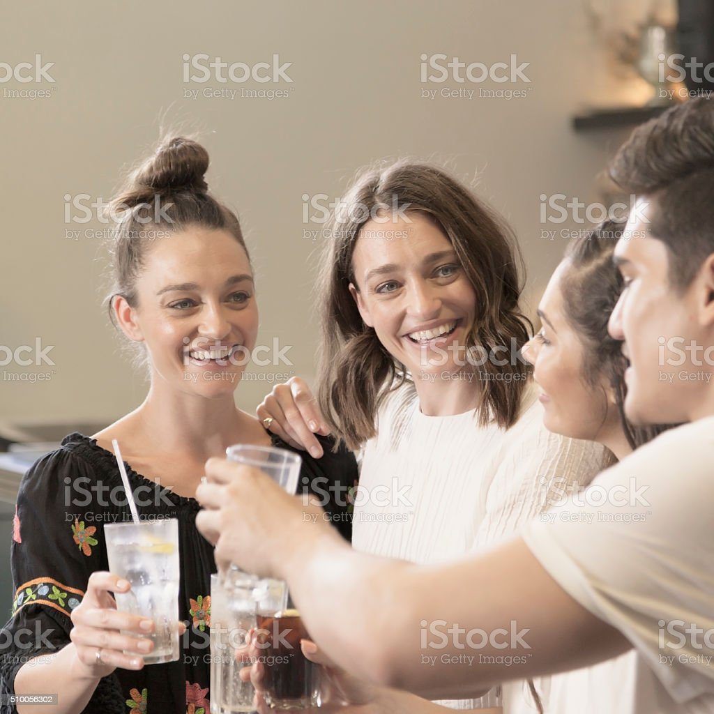 Happy young adults enjoying a pub drink stock photo