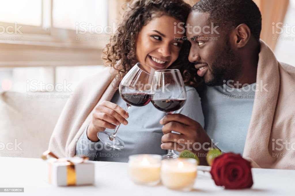Happy young African American couple drinking wine in the restaurant stock photo