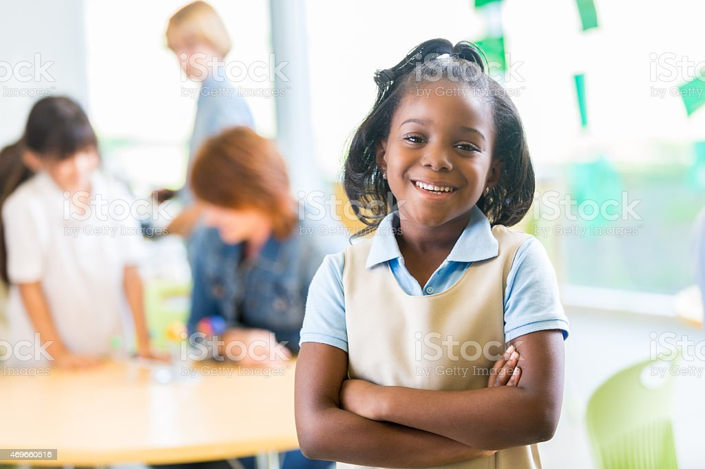 Happy young African American girl wearing private elementary school uniform stock photo