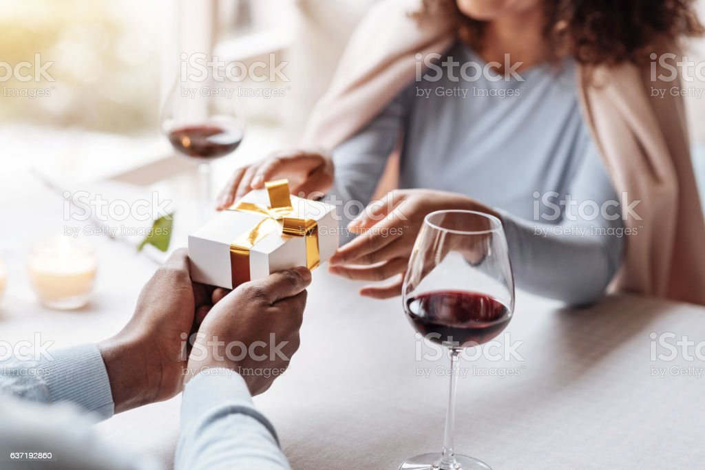 Happy young African American man congratulating his girlfriend stock photo