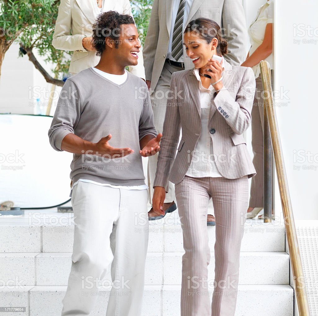 Happy young African American man walking with a woman stock photo